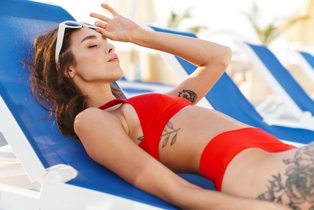 Ritratto di donna rilassata felice in occhiali da sole che riposa mentre giaceva su una sedia a sdraio in una lussuosa spiaggia soleggiata