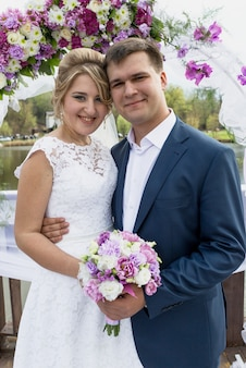 Ritratto di sposi romantici felici che si abbracciano alla cerimonia di nozze
