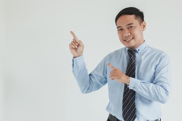 Ritratto di felice uomo di vendita che indossa camicia blu e cravatta che punta su uno spazio vuoto per la pubblicità