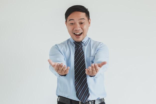 Ritratto di felice venditore che indossa camicia e cravatta blu che presenta o offre un prodotto