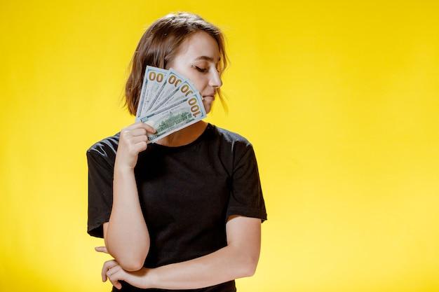 Ritratto di una ragazza soddisfatta felice che tiene in mano un mucchio di banconote e guarda la telecamera su sfondo giallo.