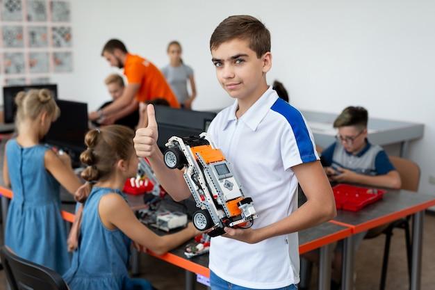 Ritratto di uno scolaro felice con un robot che lui stesso ha assemblato durante le lezioni di robotica a scuola, il ragazzo mostra un pollice in su