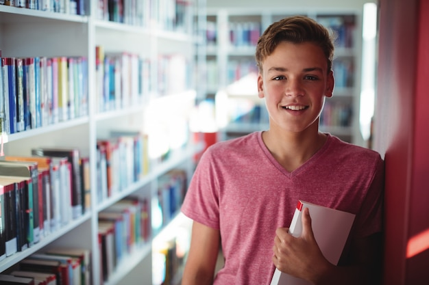 Ritratto di felice scolaro che tiene il libro in biblioteca