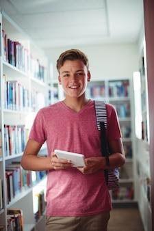 Ritratto di scolaro felice che tiene compressa digitale in libreria