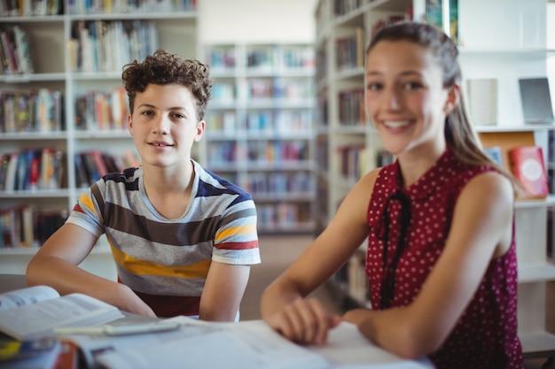 Ritratto di felice scolaro seduto con il suo compagno di classe in biblioteca
