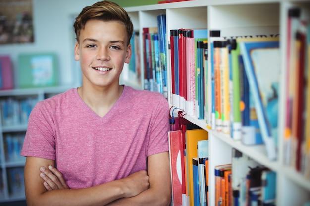 Ritratto di felice scolaro in piedi con le braccia incrociate in libreria