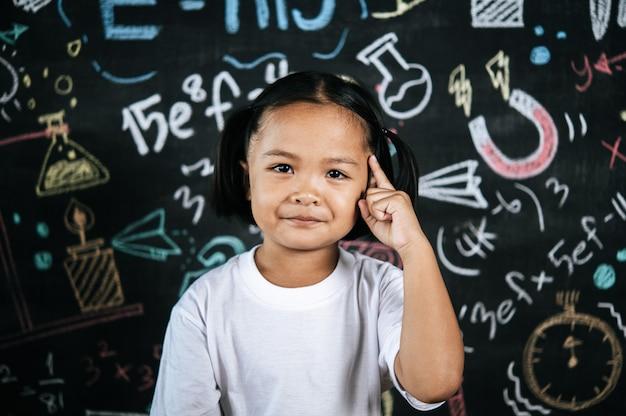 Ritratto di scolaro felice in piedi davanti alla lavagna dell'istruzione con una bella postura