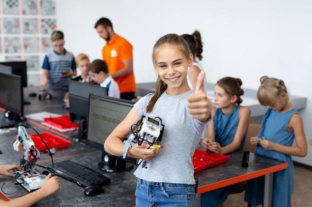 Ritratto di una ragazza studentessa felice in una classe di robotica, tiene un robot assemblato da parti in plastica programmate su un computer