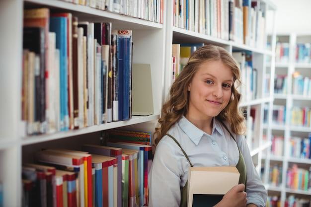 Ritratto di felice studentessa tenendo il libro in libreria