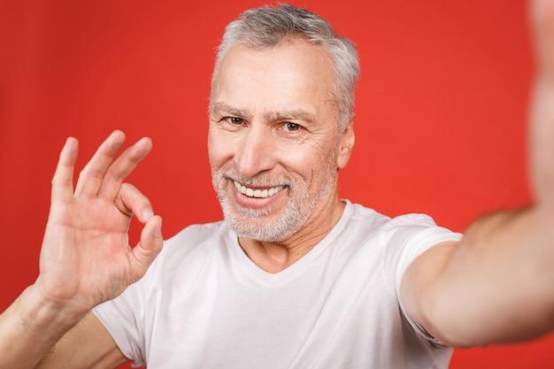 Ritratto dell'uomo barbuto senior felice che mostra segno giusto e che prende selfie sullo smartphone, isolato.