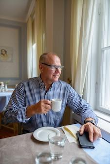 Ritratto di felice uomo d'affari senior bere caffè e guardare fuori dalla finestra a casa