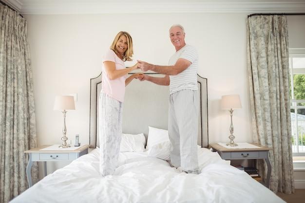 Ritratto di felice coppia senior ballare sul letto