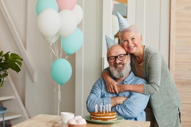Ritratto di felice coppia senior abbracciando e sorridendo alla telecamera mentre festeggia il compleanno