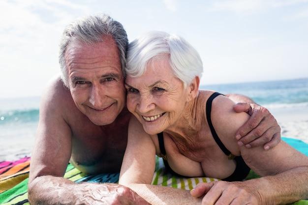 Ritratto di felice coppia senior sdraiato sulla spiaggia