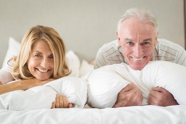 Ritratto delle coppie senior felici che si trovano sul letto