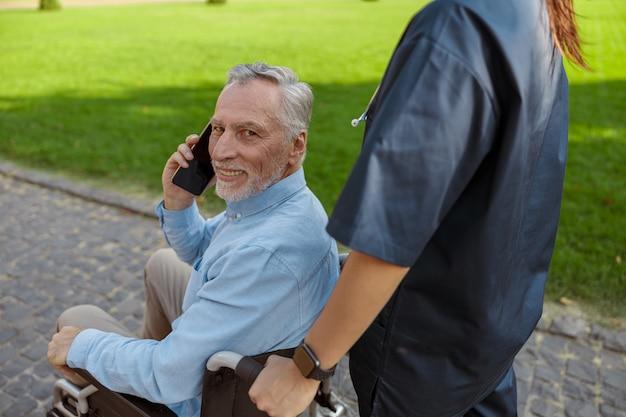 Ritratto di un uomo anziano felice che recupera un paziente in sedia a rotelle che sorride alla telecamera che parla sul