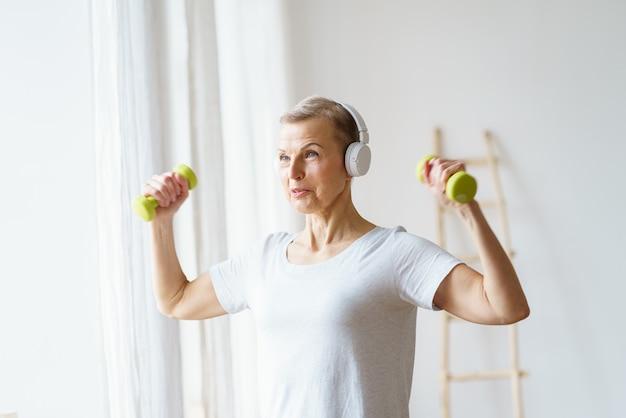 Ritratto di donna anziana felice che fa esercizio di fitness con manubri a casa femmina matura