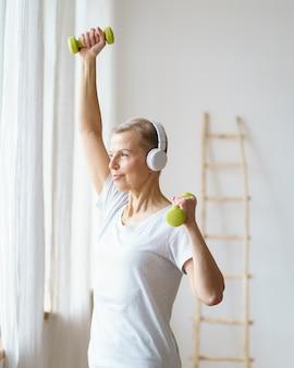 Ritratto di donna anziana felice che fa esercizio di fitness con manubri a casa
