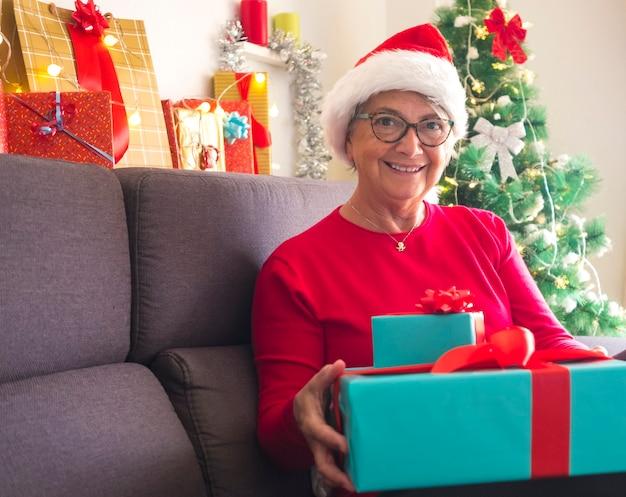 Ritratto di felice nonno donna anziana che indossa un cappello di natale seduto sul divano con in mano regali per la famiglia o gli amici con albero di natale decorato sullo sfondo