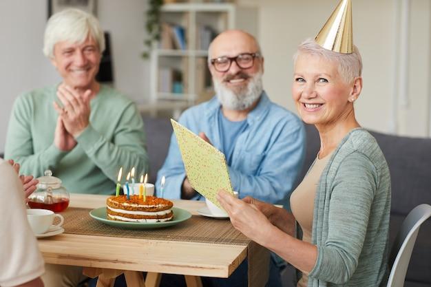 Ritratto di felice donna senior lettura biglietto di auguri e sorridere alla telecamera mentre festeggia il compleanno con i suoi amici