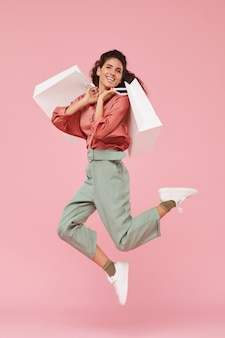 Ritratto di felice shopaholic godendo i suoi acquisti lei salta con i sacchetti della spesa sullo sfondo rosa