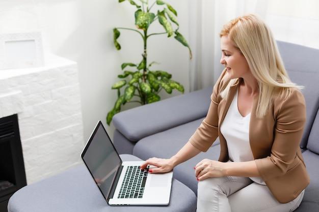 Ritratto di felice esperta donna di mezza età life coach, consulente aziendale, psicologo o consulente medico che sorride con gioia alla macchina fotografica, lavora al laptop, si gode il suo lavoro, aiuta le persone online