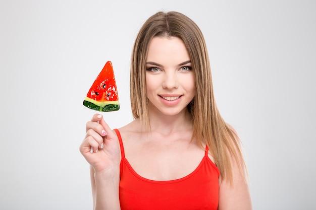 Ritratto di felice sorridente contenuto attraente giovane donna con gustoso rosso dolce a forma di anguria lecca-lecca