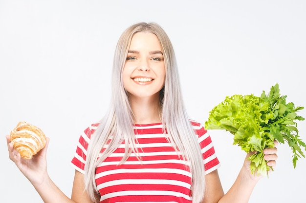 Ritratto di una bella giovane donna bionda sorridente felice che sceglie tra un alimento sano e malsano. isolato su sfondo bianco.