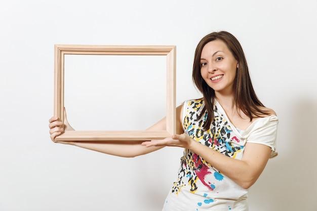 Il ritratto di una donna dai capelli castani sorridente felice in piedi e che tiene una cornice di legno vuota sullo sfondo bianco. con posto per il testo per la pubblicità.