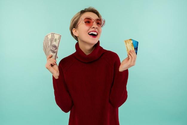 Ritratto della donna caucasica sorridente felice che tiene la carta di credito e soldi dei dollari degli sua mentre esamina la macchina fotografica isolata sopra fondo blu.