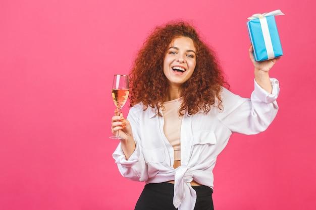 Ritratto di una ragazza riccia sorridente felice che apre una confezione regalo