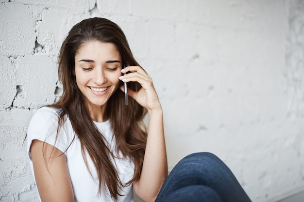 Ritratto della femmina europea sorridente felice che si siede sul pavimento e che si appoggia sul muro di mattoni bianco mentre parla sullo smartphone con il buon amico. grazie a dio abbiamo il wifi quasi ovunque
