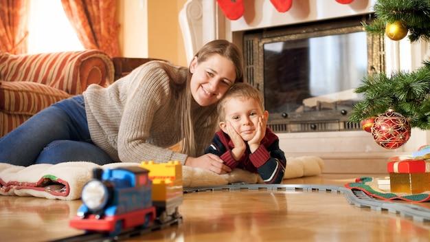 Ritratto di una famiglia sorridente felice sdraiata sul pavimento e guardando il treno che viaggia sulla ferrovia sotto l'albero di natale in soggiorno