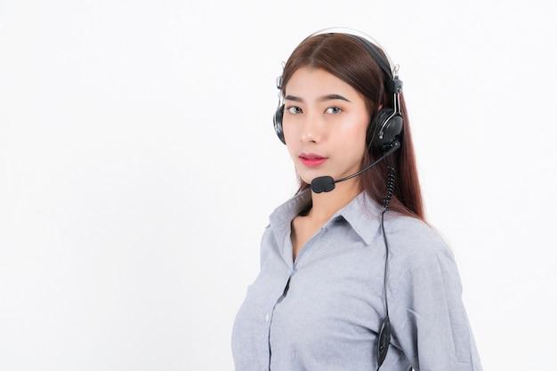 Ritratto di capelli corti sorridente felice dell'operatore telefonico di assistenza clienti femminile, indossa una camicia grigia con auricolare