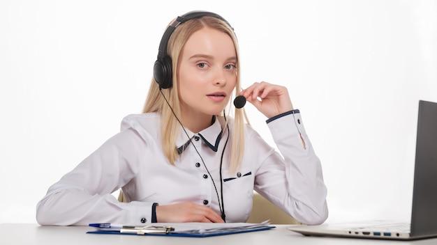 Ritratto di felice sorridente operatore telefonico di assistenza clienti femminile sul posto di lavoro. - immagine