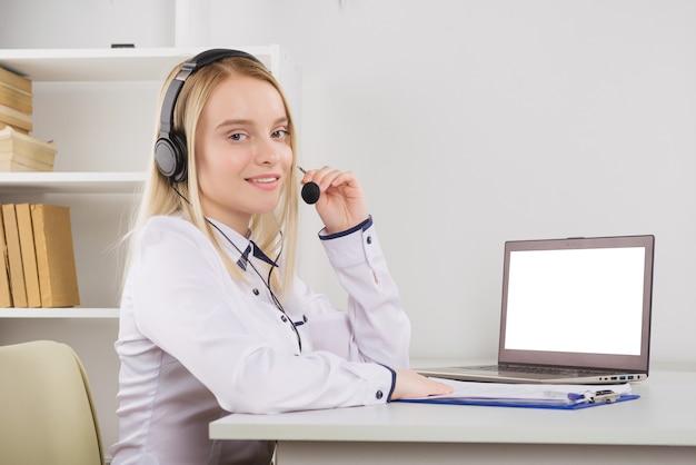 Ritratto di felice sorridente operatore telefonico di assistenza clienti femminile sul posto di lavoro.