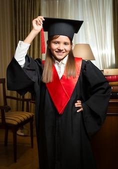 Ritratto di ragazza sorridente felice in cappello di laurea e abito in posa all'interno classico