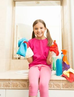 Ritratto di ragazza sorridente felice in guanti di gomma in posa con uno straccio in bagno