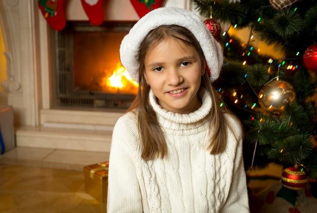 Ritratto di una ragazza sorridente felice con un cappello da babbo natale seduto accanto al caminetto acceso