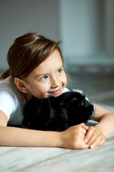 Ritratto di bambina sorridente felice che abbraccia cavia nera.