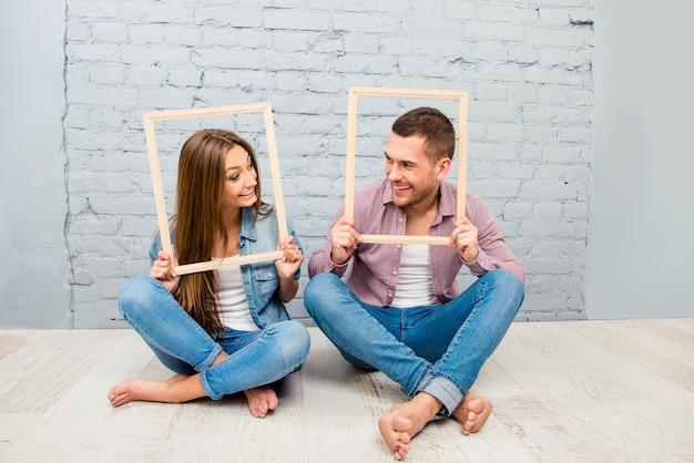 Ritratto di uomo sorridente felice e donna in posa all'interno dei telai