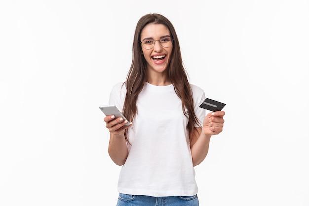 Ritratto di donna graziosa sorridente felice in bicchieri tenendo la carta di credito, telefono cellulare, ridendo fotocamera facilmente pagando per il suo negozio online di acquisto