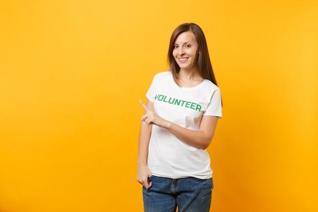 Ritratto di donna soddisfatta sorridente felice in maglietta bianca con iscrizione scritta volontario titolo verde isolato su sfondo giallo. aiuto volontario di assistenza gratuita, concetto di lavoro di grazia di carità.