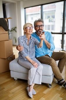 Ritratto di felice coppia senior sorridente innamorata che si trasferisce in una nuova casa