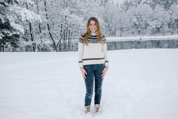 Ritratto dell'adolescente sorridente felice o della giovane donna all'aperto nel parco di inverno