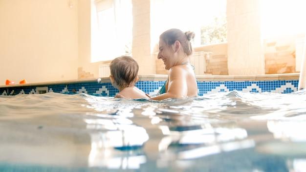 Ritratto del ragazzo sorridente felice del bambino che impara a nuotare con la madre in piscina. famiglia che si diverte e si rilassa in piscina