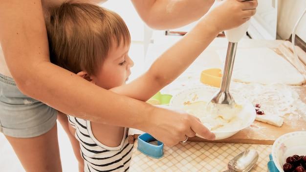 Ritratto del ragazzo sorridente felice del bambino con la giovane madre che cuoce e che cucina sulla cucina. genitore che insegna ed educa il bambino a casa