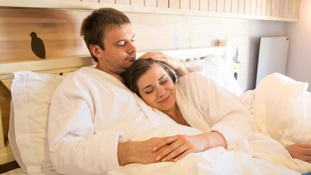 Ritratto di donna sorridente felice che abbraccia suo marito sdraiato a letto in una camera d'albergo