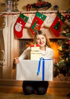 Ritratto di donna sorridente felice in posa con scatole presenti al caminetto