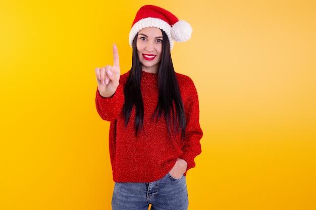 Ritratto felice, sorridente donna che indossa x'mas santa cappello, mostrando un dito. contenuto sconto di natale.
